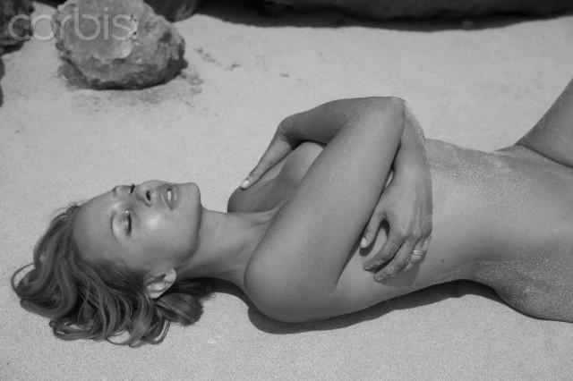 Shirtless woman lying on sand
