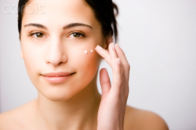 Close up of a young woman applying moisturizer on her cheek