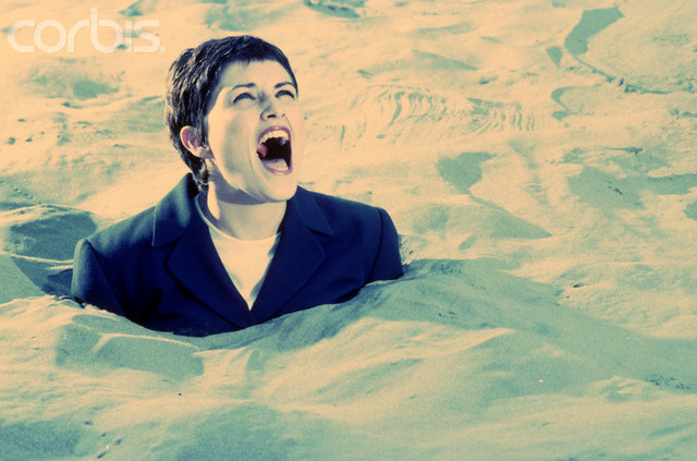 Screaming businesswoman buried in sand