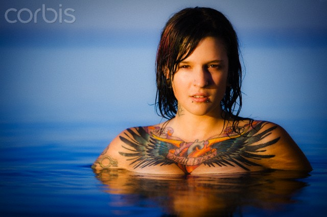 Portrait tattooed woman 20's emerging from the water in a lake at sunset.