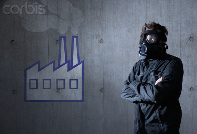 Man in a jump suit and gas mask in front of a wall with a picture of a factory