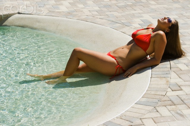 Woman in red bikini lying near swimming pool