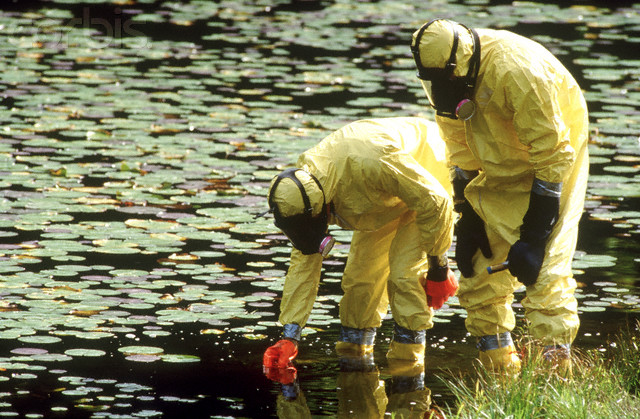 Workers in protective suits sampling lakewater