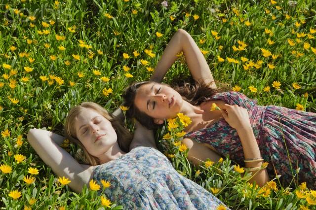 Teenage girls laying in field of flowers
