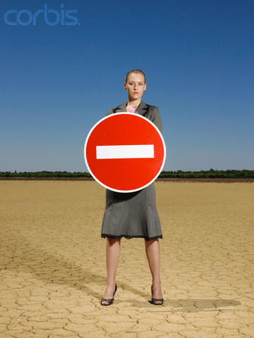 Businesswoman in Desert Holding Do not Enter Sign